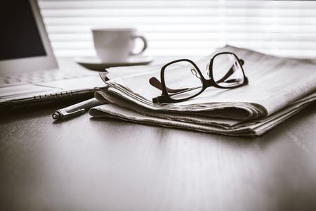 테이블에 컴퓨터와 신문 읽기 스톡 콘텐츠