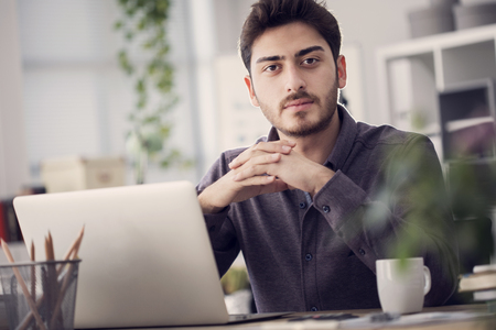 Young man works on his laptop