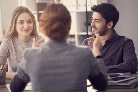 Young couple discussing with a female agent Stock Photo