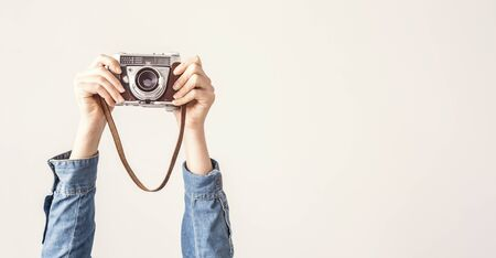 Arms up holding vintage camera isolated background Foto de archivo