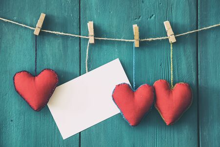Hanging red heart shapes with with message paper wooden background