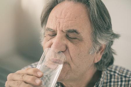Senior man drinking glass of water inside