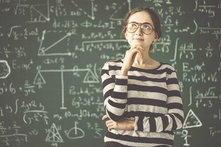 Young female student thinking in front of classroom board