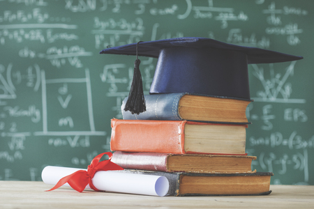 Stack books  graduate hat and diploma in front of  green chalkboard Banque d'images