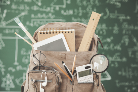 Backpack school with supplies in front of  green chalkboard