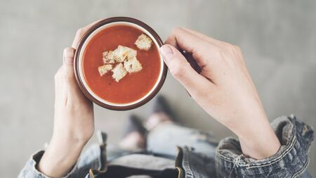Woman holding tomato soup cup with croutons Stock Photo