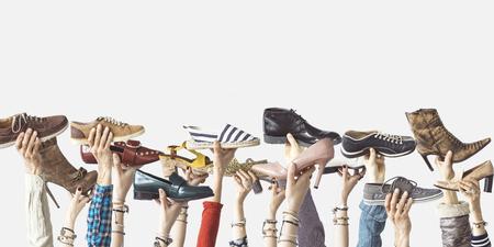 Manos sosteniendo diferentes zapatos sobre fondo aislado