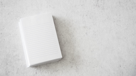 Stack of white notepapers on white table