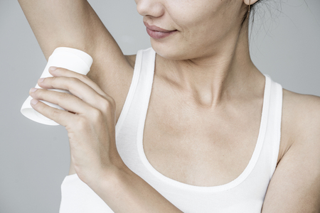 Woman applying deodorant on her armpit