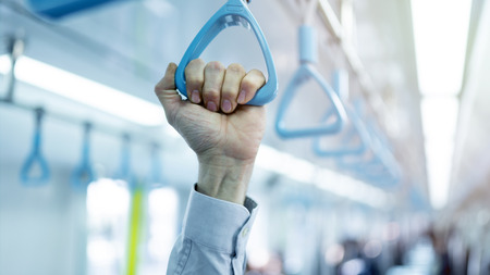 Man hand holding handle on the train
