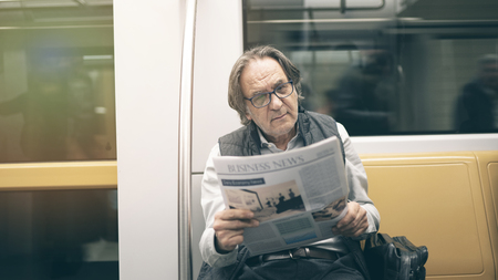 Man reading newspaper in the metro train Imagens