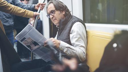 Man reading newspaper in the metro train Stockfoto