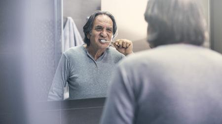 Viejo cepillarse los dientes frente al espejo