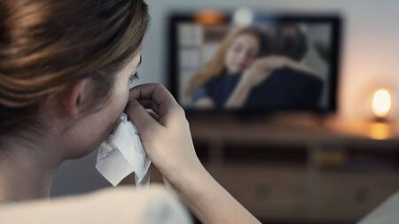 Woman crying while watching tv in the night