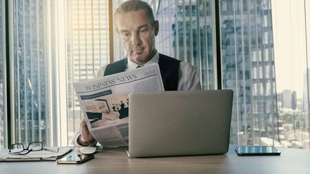 Businessman reading newspaper at office