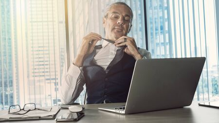 Businessman loosening necktie in the office