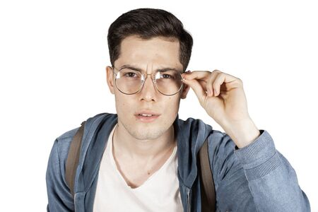 Young man looking over glasses curiously