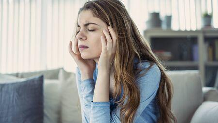Young woman with headache in home Zdjęcie Seryjne