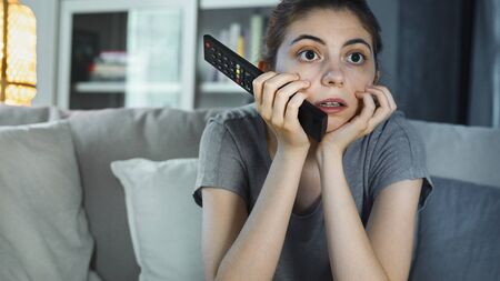 Young girl watching tv at home