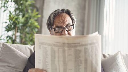 Senior man reading newspaper at home Archivio Fotografico