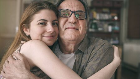 Cute young daughter embracing her father with love