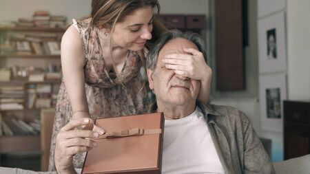 Young daughter embracing her father with love and giving present