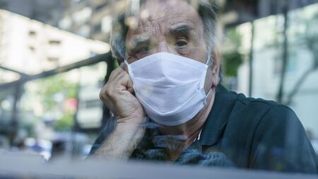 Man looking out window with mask Archivio Fotografico