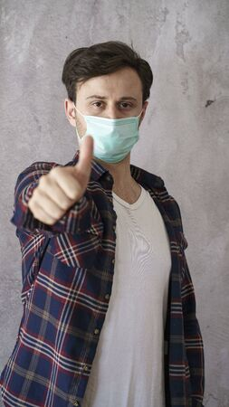 Man showing thumb up with face protective mask
