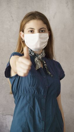 Young woman showing thumb up with face protective mask