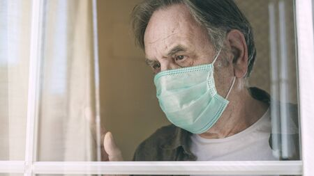 Old man looking through the window and waving hand with mask protection
