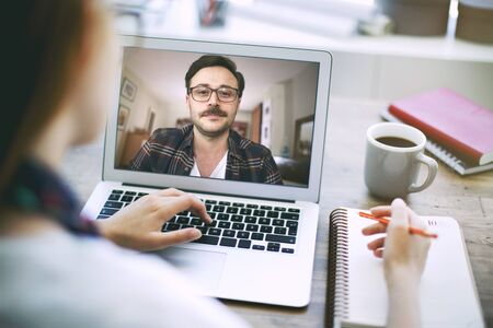 Woman talking to her colleague about plan in video conference