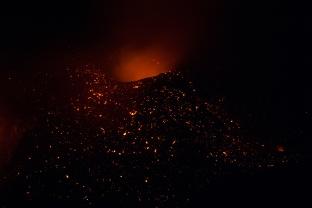 Stromboli after the explosion in the night with smoke and lava light