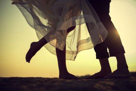 bride and groom kissing at sunset with their feet on wet sand Stock Photo