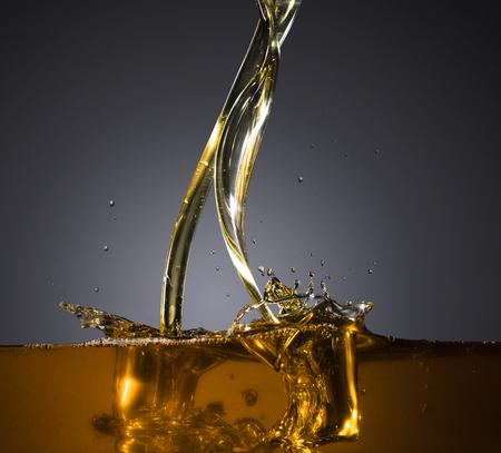 Close-up di olio e liquido versando su sfondo scuro.