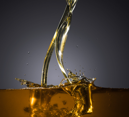 Close-up of oil and liquid pouring on dark background. Stock Photo