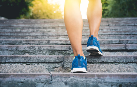 Fitness woman running up the old stairs. Legs running and burn out fat for fit body, Healthy and lifestyle concept poster Imagens