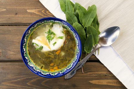 Diet sorrel soup with egg. on a wooden table.
