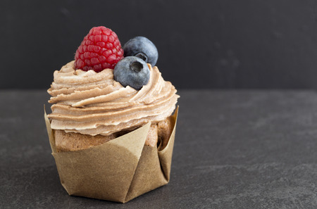 Chocolate cupcake with cream, blueberries and strawberries.