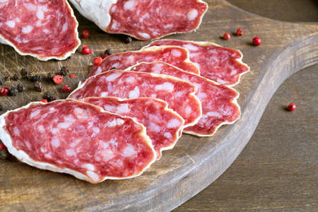 slices of French cheese-dried salami with spices on wooden background Archivio Fotografico