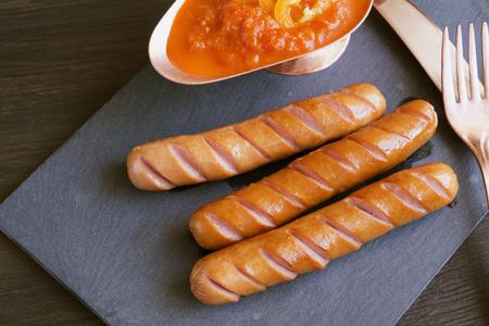 Saucisse frite sur une planche en pierre noire. Banque d'images