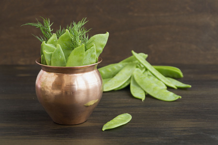 Young fresh green peas on wooden background.