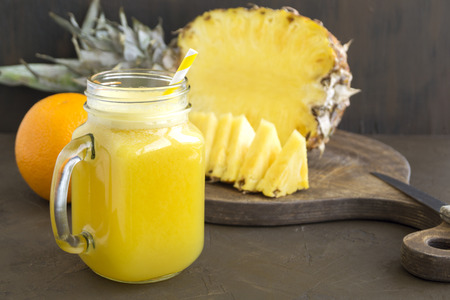 Pineapple juice in a jar with a straw.