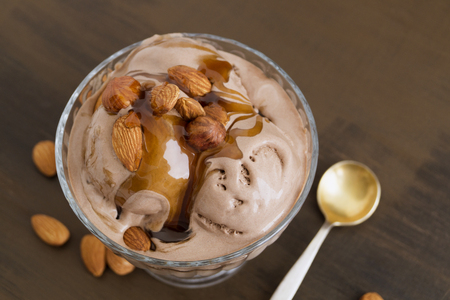 chocolate ice cream in a glass vase. on a wooden background.