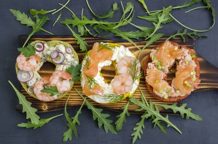 Bagels with cream cheese, salmon, shrimp. On a black background. 写真素材 - 137800820