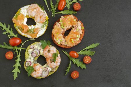 Bagels with cream cheese, salmon, shrimp. On a black background.
