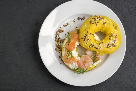 Bagels with cream cheese, salmon,  shrimp. On a black background. 写真素材 - 137800815