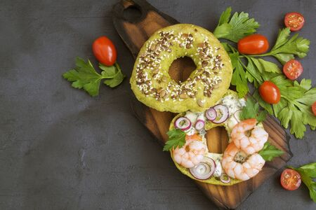 green bagel with cheese and shrimp. on a gray background.