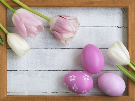 Easter composition. Easter eggs, photo frame, tulips on a white wooden background. Flat layout, top view, copy space. Archivio Fotografico - 140020682