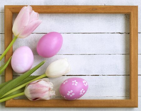 Easter composition. Easter eggs, photo frame, tulips on a white wooden background. Flat layout, top view, copy space. Archivio Fotografico - 140020686