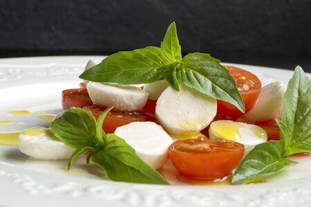 Caprese salad with ripe tomatoes and mozzarella with fresh Basil leaves. Italian food. Standard-Bild
